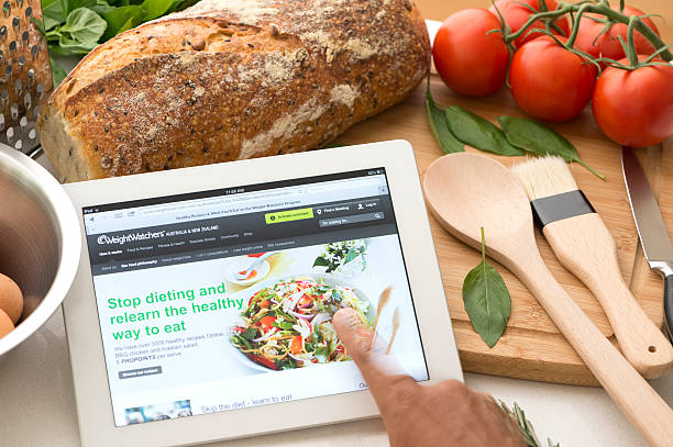 weightwatchers.com website on a digital tablet in a kitchen - ww dot com stock photos and pictures