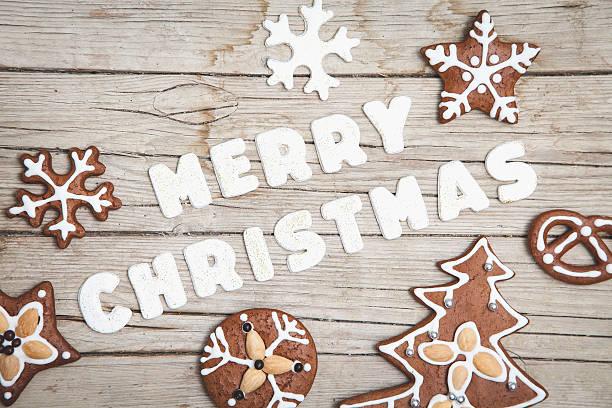 weihnachtlicher grauer holz hintergrund mit lebkuchen und merry - weihnachtsplätzchen rezepte stock-fotos und bilder