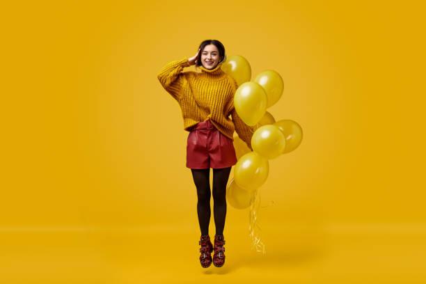 weird female with balloons jumping and saluting - mulher balões imagens e fotografias de stock