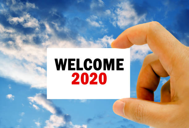 welcome 2020 on business card clouds background stock photo