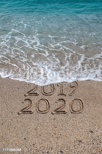 New year 2020 written on sandy beach with waves