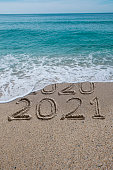 New year 2021 written on sandy beach with waves