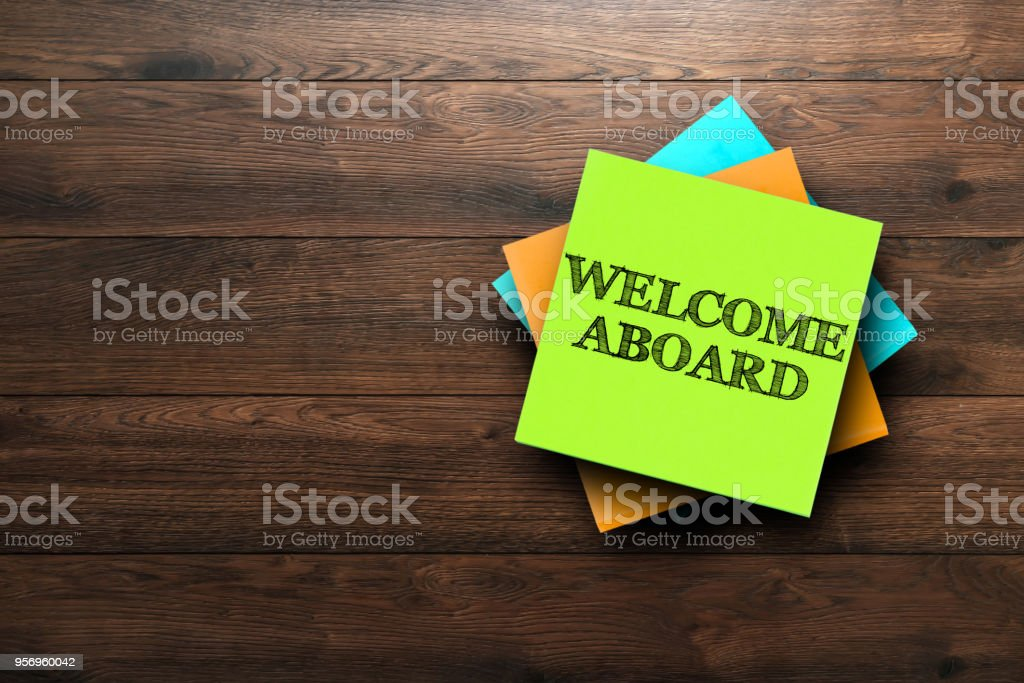Welcome Aboard, the phrase is written on multi-colored stickers, on a brown wooden background. Business concept, strategy, plan, planning. stock photo
