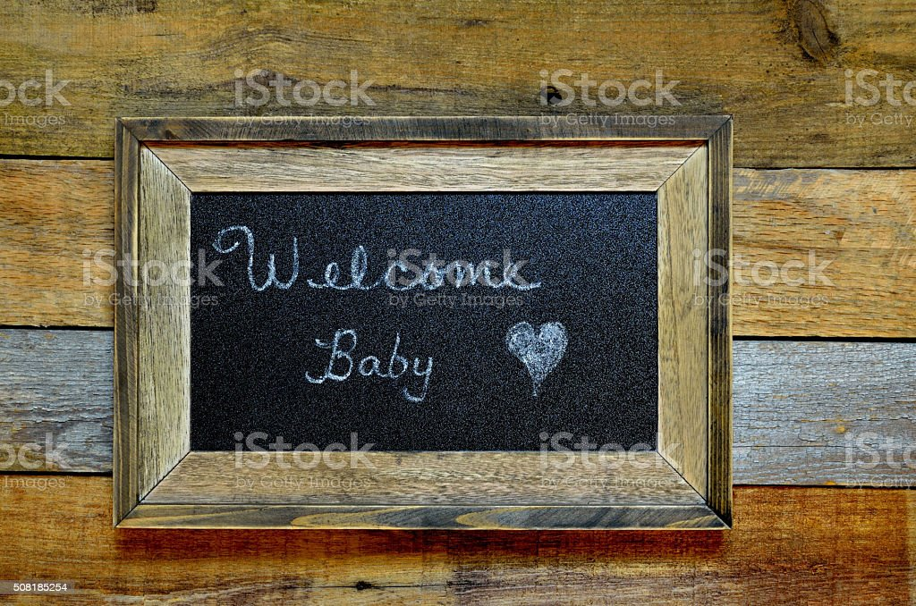 Welcome baby announcement on rustic framed blackboard stock photo