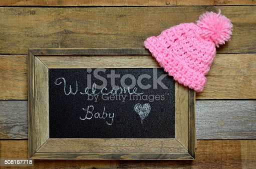 istock Welcome baby notice with pink knit cap 508167718