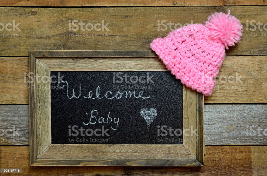 Welcome baby notice with pink knit cap stock photo