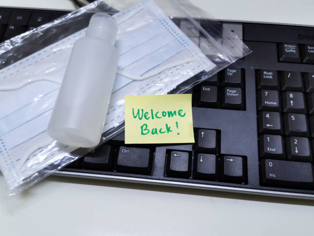 welcome back note with hand sanitizer and mask on top of keyboard - destination stock pictures, royalty-free photos & images