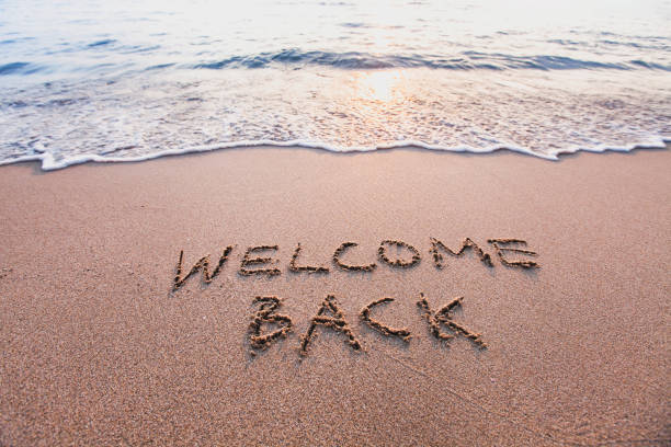 welcome back, text on sand beach, tourism concept stock photo