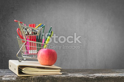 istock Welcome back to school concept with blank black chalkboard background for copy space  and school supplies in shopping card on dark wood 960667192