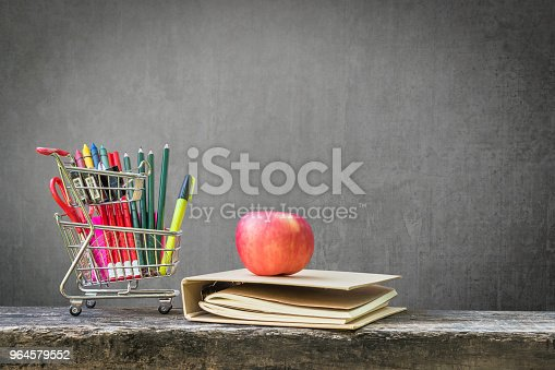 istock Welcome back to school concept with blank black chalkboard background for copy space  and school supplies in shopping card on dark wood 964579552
