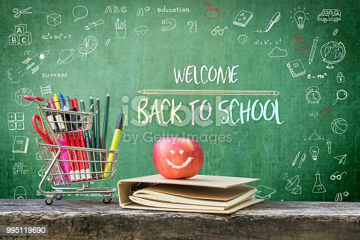istock Welcome back to school, educational greeting announcement for students and teacher on green chalkboard with creative kid's doodle drawing and stationary supplies, book and apple 995119690