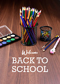 Art supplies on a wooden background. School supplies for painting. Back to School lettering with crayons images