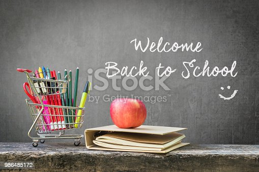 972347304istockphoto Welcome back to school  with shopping cart, school supplies, stationery, notebook, apple on wood table top and black teacher chalkboard 986485172