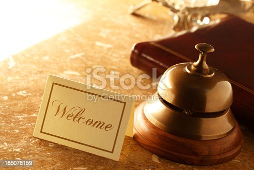 A service bell and a welcome card at a hotel desk.