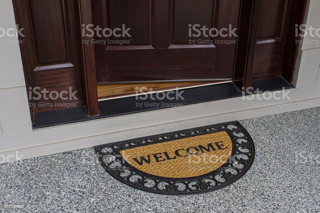 Welcome door mat with open door stock photo