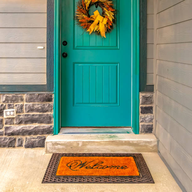Welcome doormat in front of a door with wreath Welcome doormat in front of a door with wreath. A welcome doormat in front of the blue green door of a home. A festive wreath with golden bow is hanging on the lovely front door. front door stock pictures, royalty-free photos & images