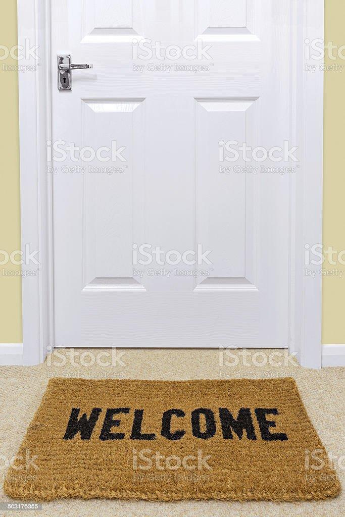 Welcome doormat outside a door. stock photo