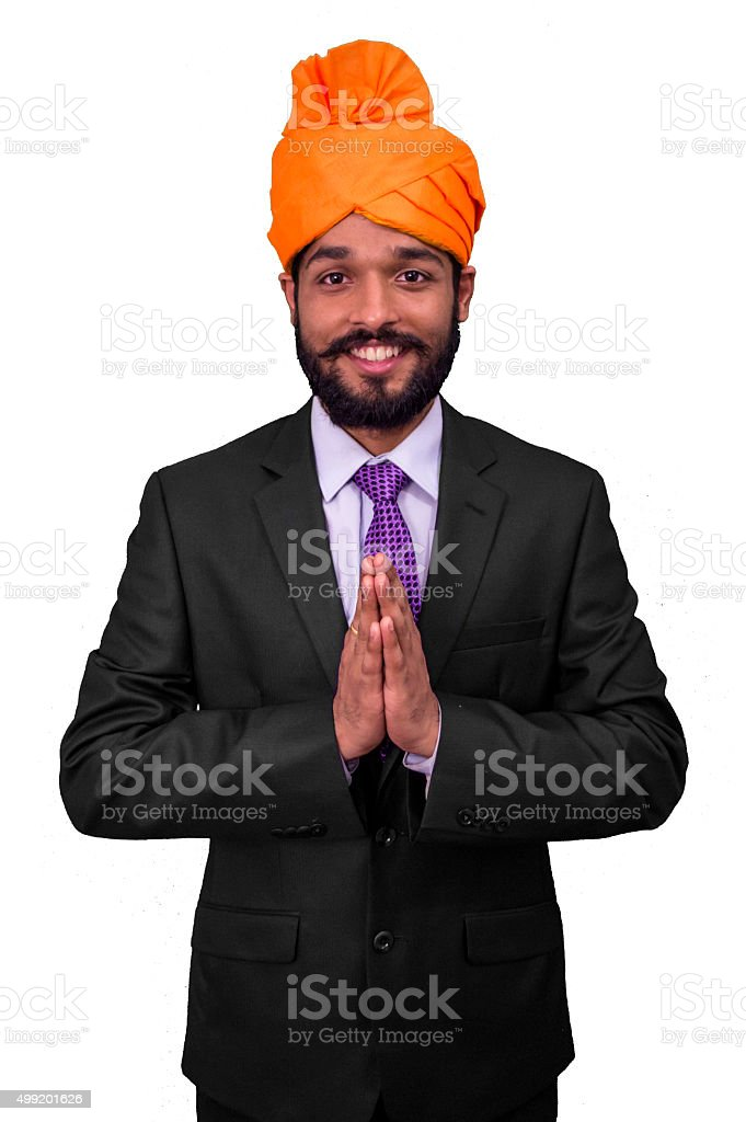 Welcome gesture by an Indian business man wearing orange turban. stock photo