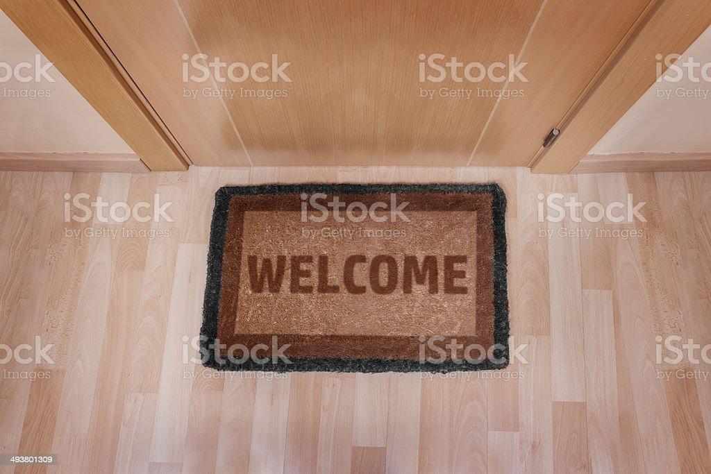 Welcome home doormat with closed door stock photo