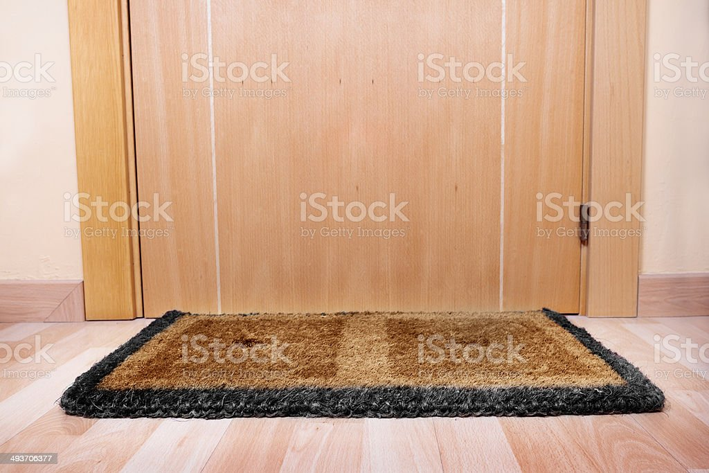 Welcome home doormat with open door royalty-free stock photo