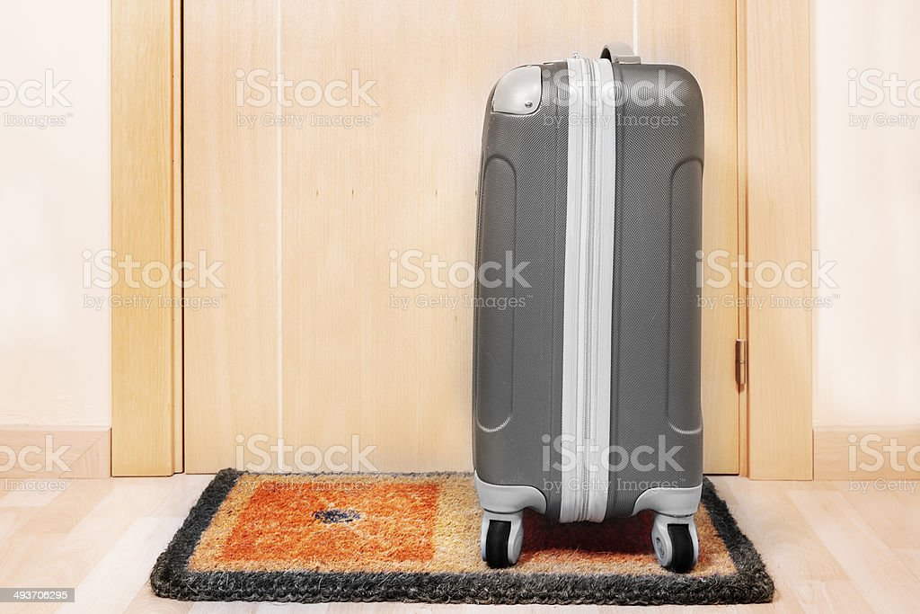 Welcome home doormat with suitcase royalty-free stock photo