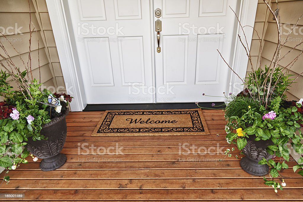Welcome Home entrance double doorway flowers in pots stock photo