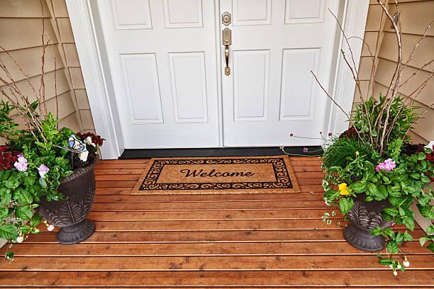 welcome home eingang mit zwei türen blumen in töpfen - verandas stock-fotos und bilder