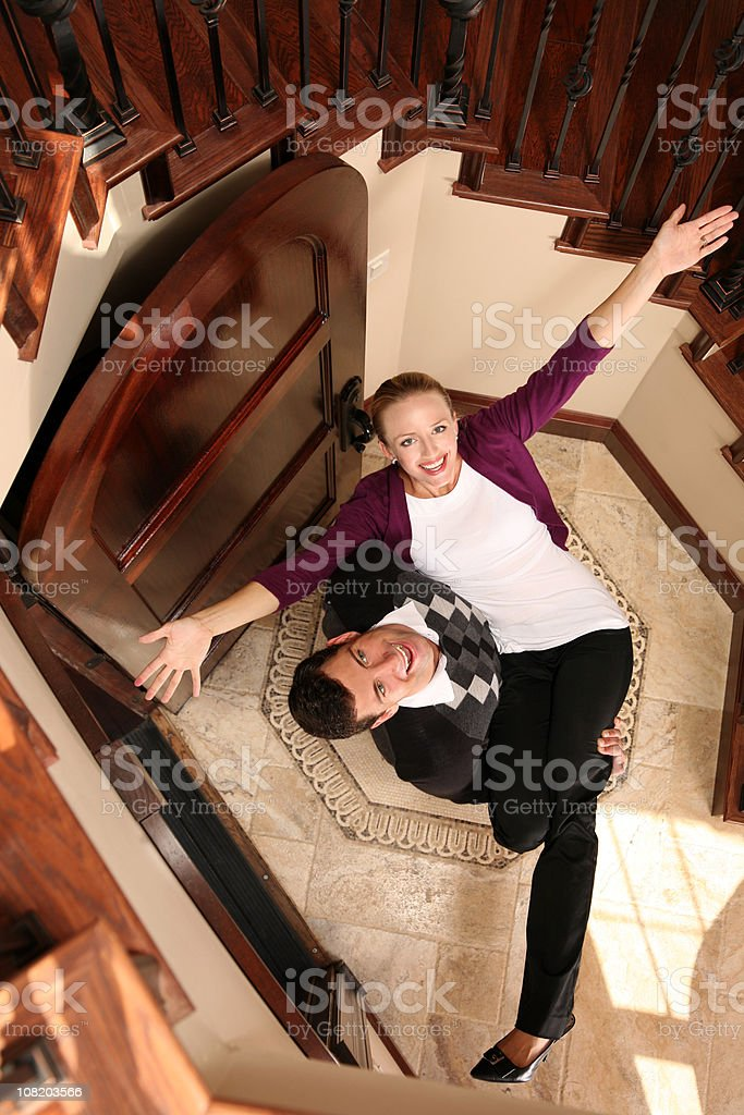 Welcome home - Husband carries Wife over threshold front door royalty-free stock photo