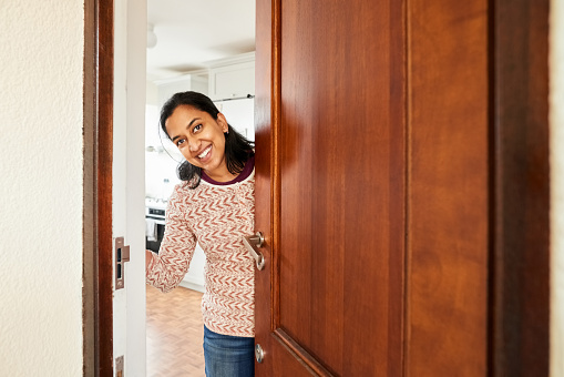 Shot of a happy female opening front door of her home with a smile