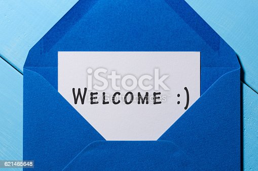 istock Welcome inscription. Hand drawn letter in blue envelope 621465648