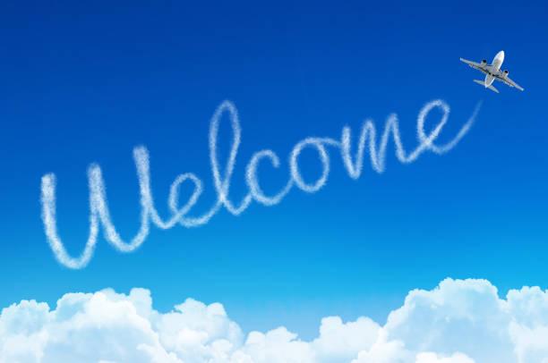 willkommen - inschrift am himmel mit dem flugzeug verlassen. - russisch hallo stock-fotos und bilder