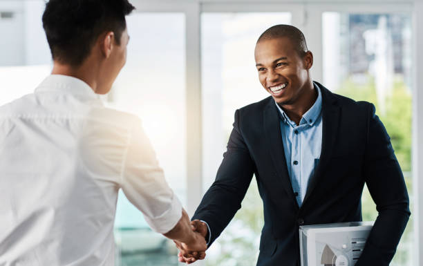 Welcome, let's get started Shot of two young businessmen shaking hands in a modern office job interview stock pictures, royalty-free photos & images