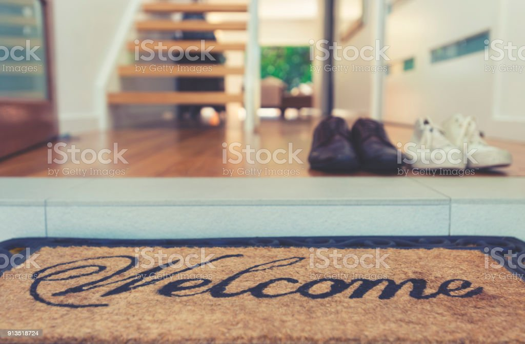 Estera de bienvenida en la puerta abierta. - foto de stock