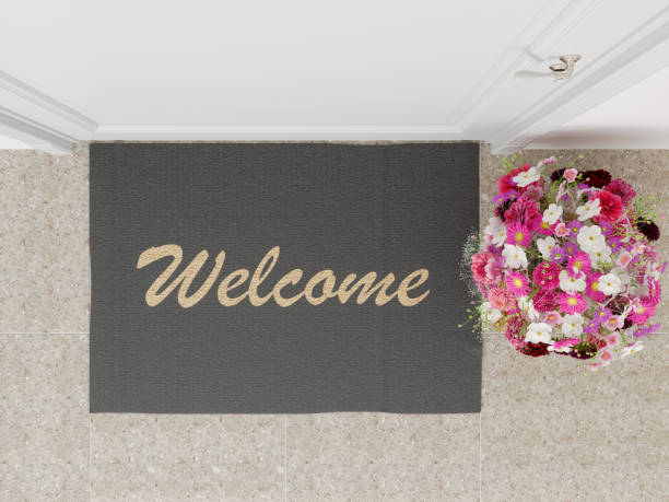 Welcome mat with flower at the front door overhead top view stock photo