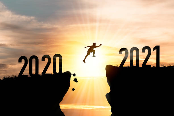 välkommen god jul och gott nytt år i 2021,silhouette man hoppa från 2020 klippa till 2021 klippa med moln himmel och solljus. - calendar workout bildbanksfoton och bilder