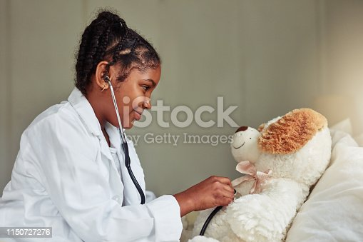 Shot of a young girl pretending to be a doctor while while playing with her teddybear