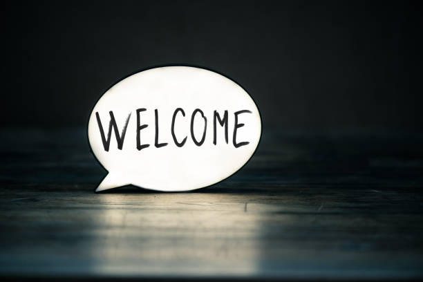 Welcome Lightbox in form of a Speech bubble showing the word welcome on wood desk . welcome sign stock pictures, royalty-free photos & images