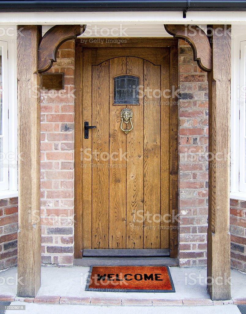 Welcome Old Oak Door with Welcome Mat. Brass Stock Photo