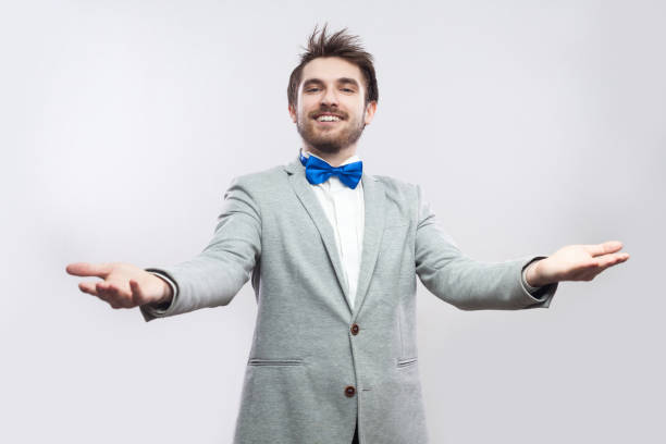 756eb6f3ae74 Portrait of happy handsome bearded man in casual grey suit and blue bow tie