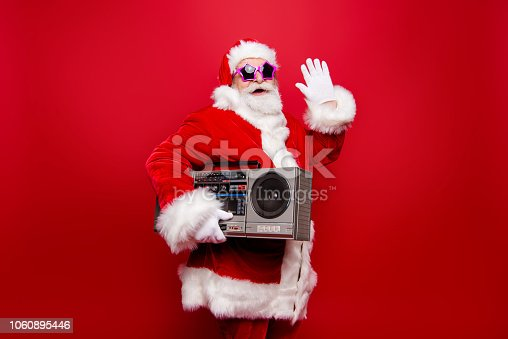 istock Welcome! Profile side view positive grandfather aged mature Santa tradition costume headwear star spectacles hold vintage player waving hello hi goodbye isolated noel winter desember red background 1060895446