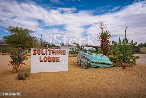 Solitaire, Namibia - March 29, 2019 : Welcome sign at the Solitaire Lodge with a car wreck. Solitaire is a small settlement in the namibian desert near the Namib-Naukluft National Park.