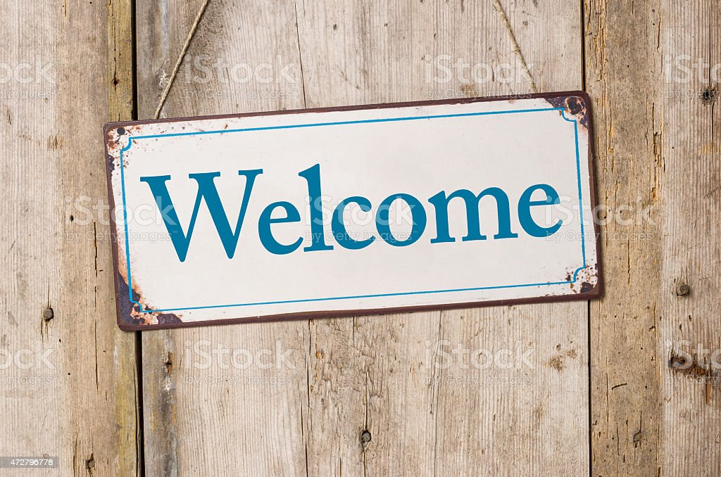 A welcome sign hanging on a wooden door stock photo
