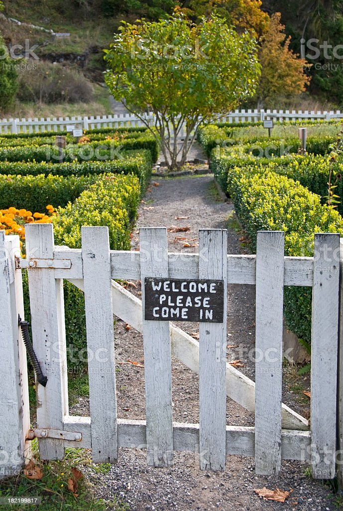 Welcome sign on white gate into garden with hedges royalty-free stock photo