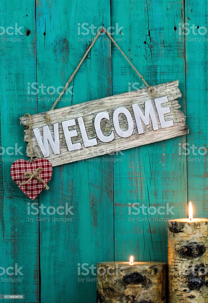 Welcome sign with candles and heart on antique blue background stock photo