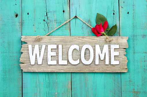 Welcome sign with red rose bud