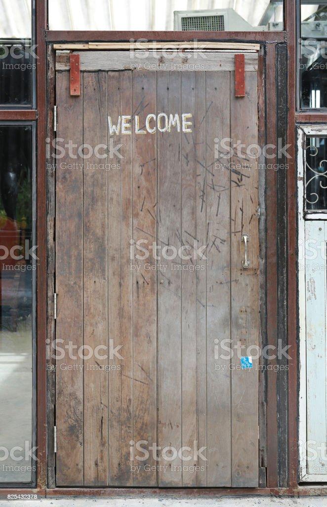 welcome sign written by chalk on wood door background open door