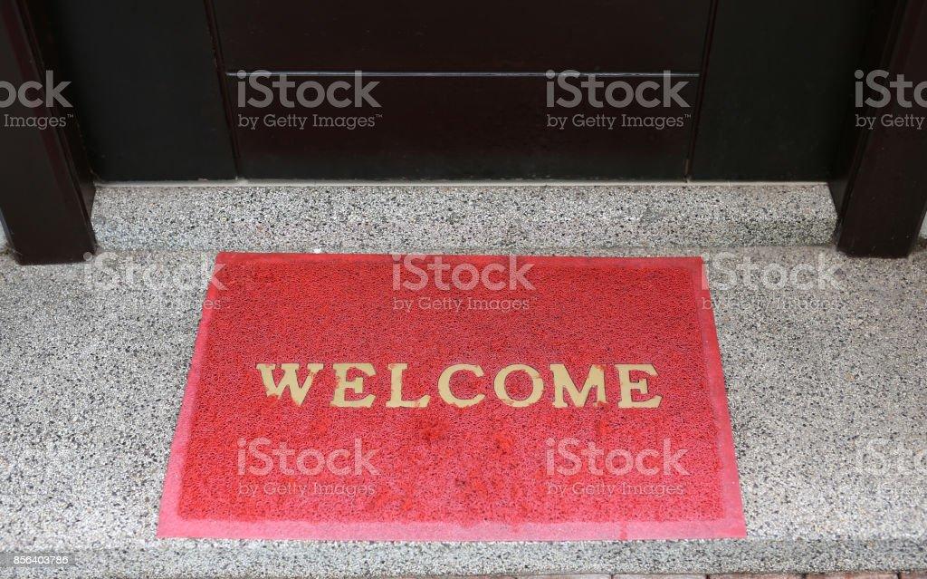 welcome text on red doormat in front of door room. stock photo