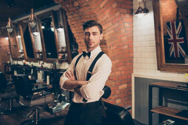 hoş geldin berber dükkanı! çekici genç esmer adam ile kıl çapraz elle, ayakta bir kuaför dükkanında bir retro tarzı şık giyinmiş. sıcak ve seksi - pantolon askısı stok fotoğraflar ve resimler