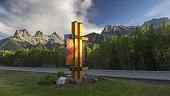 Road Sign along Highway 1A with Iconic Three Sisters Mountain in the background at Foothills of Rocky Mountains Alberta Canada