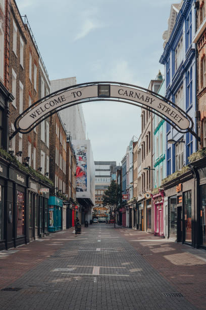 Welcome to Carnaby Street Sign over empty Carnaby Street in Soho, London, UK. London, UK - June 13, 2020: Welcome to Carnaby Street Sign over empty Carnaby Street. Carnaby Street is a famous pedestrianised shopping street in the Soho area of London. carnaby street stock pictures, royalty-free photos & images